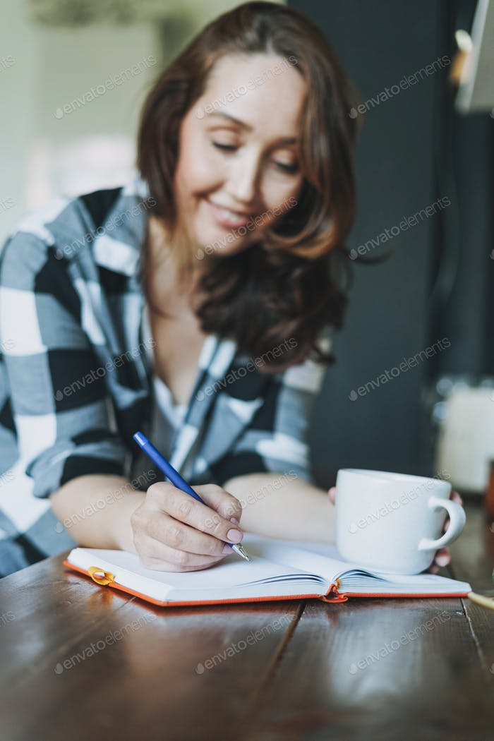 Adult smiling brunette woman in casual doing notes in daily book with cup of tea