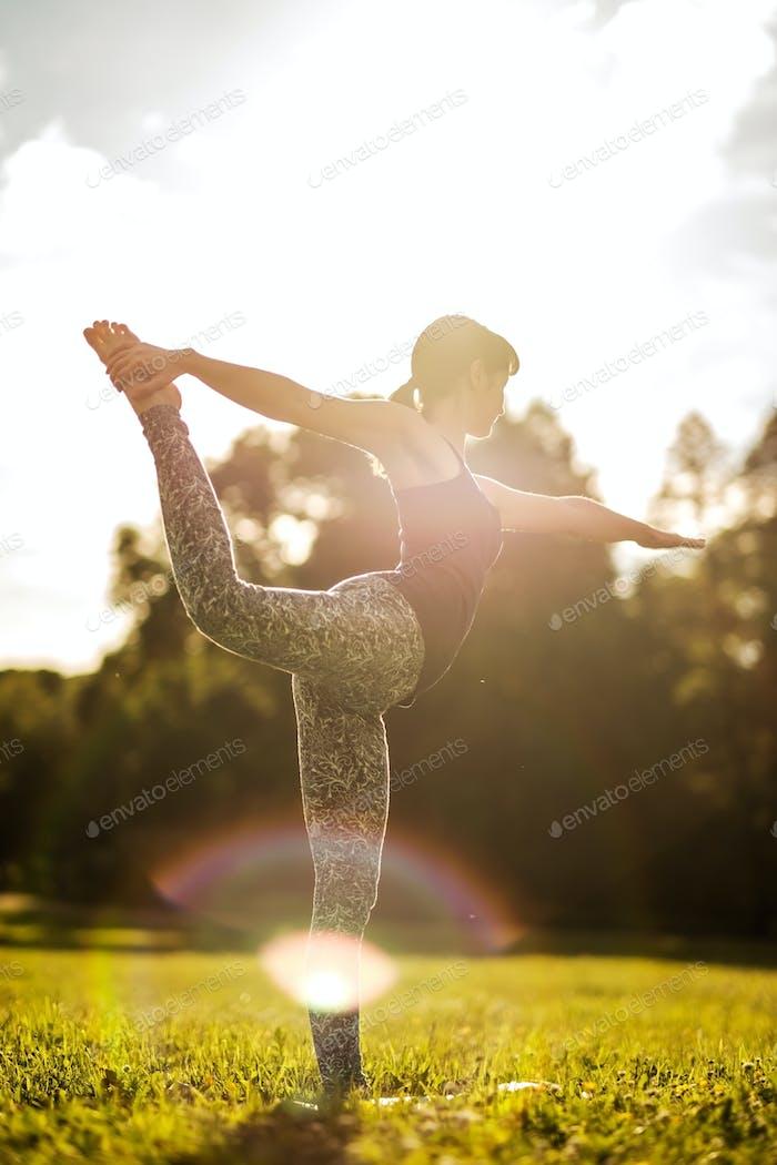Caucasian woman in yoga standing balance Natarajasana. Back view