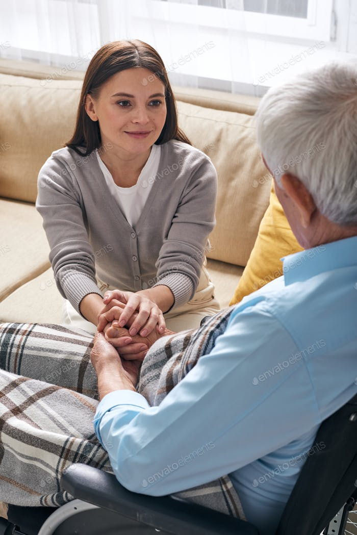 Pretty young brunette female holding hands of aged disable man
