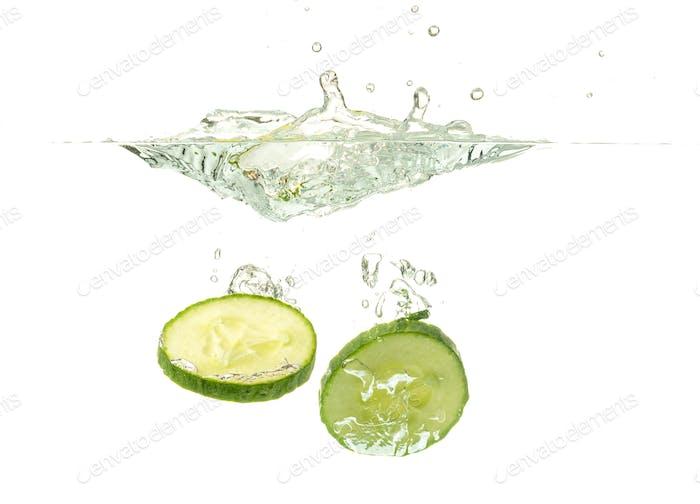 Sliced cucumber splashing water isolated on white background. Skin moisturizing cosmetics