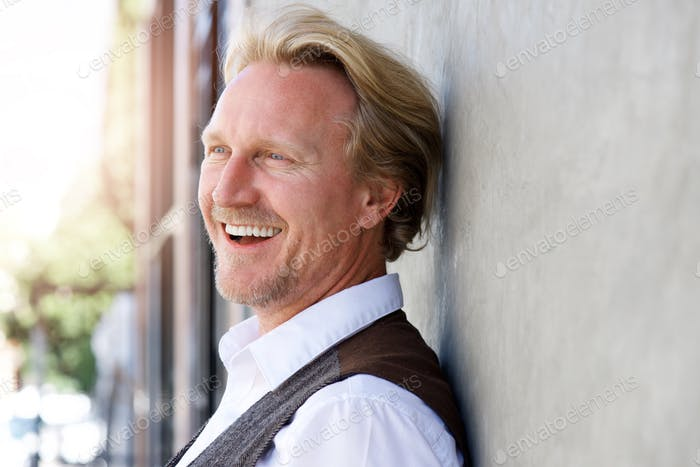 Middle aged caucasian man leaning to wall and laughing
