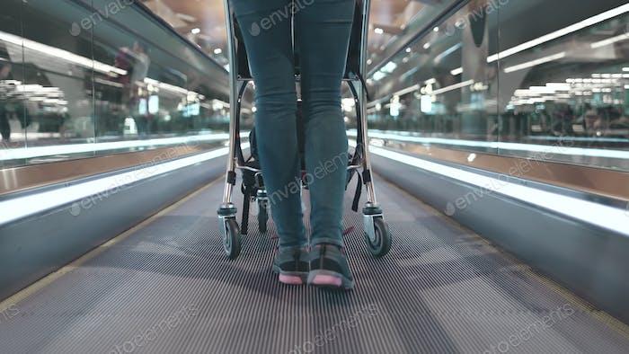 Frau mit Gepäckwagen am Flughafen Terminal Lobby