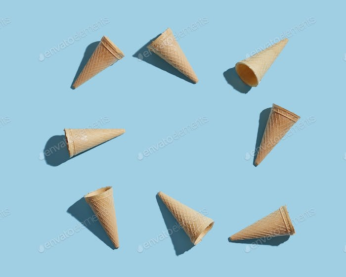Ice cream empty cones pattern on a blue paper background. Flat lay