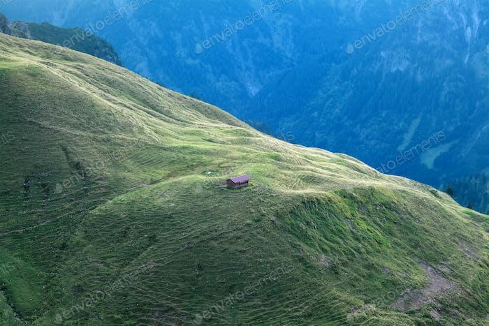 old wooden cabin on hill in Alps