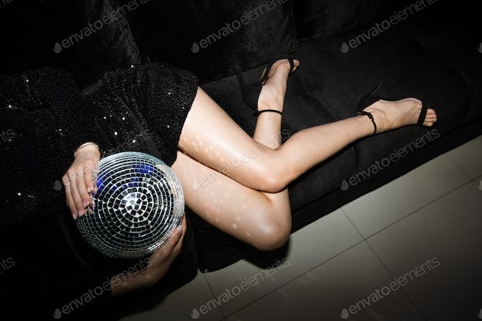 Slim legs of young woman in black glittering mini dress holding disco ball