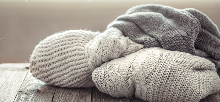 A cozy stack of knitted sweaters on a wooden background.