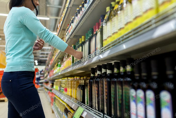 woman choosing olive oil at supermarket or grocery