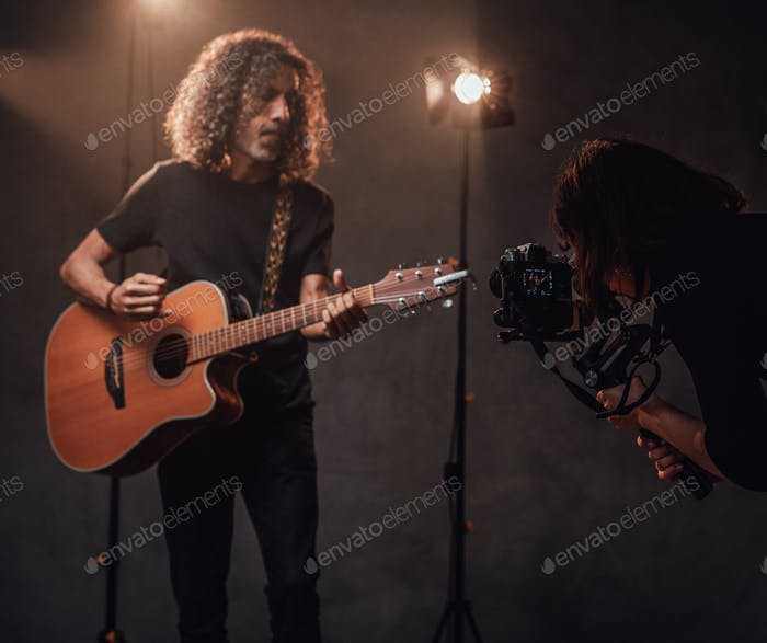Videographer shoots how a talented Latin American musician playing guitar in the studio