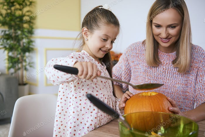 Mother helping daughter in carving pumpkins