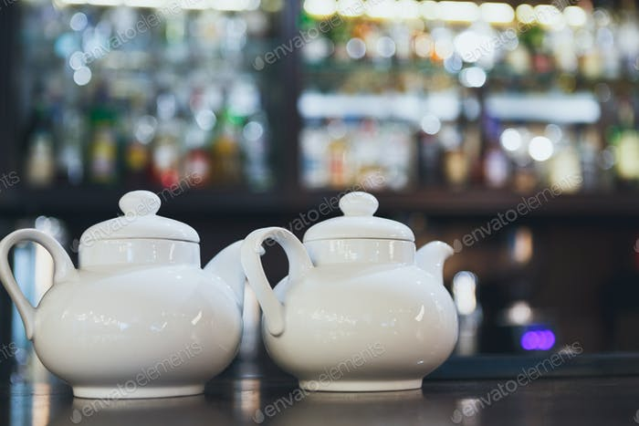 Bar counter with two white teapots