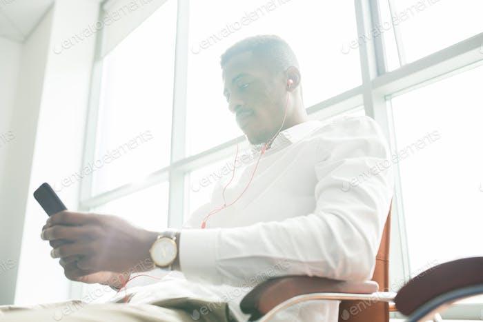 Serious businessman in earphones watching video on smartphone