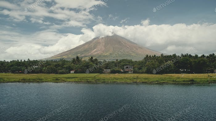 Volcano erupt at green lake shore aerial. Philippines coutryside of Legazpi town at greenery meadows