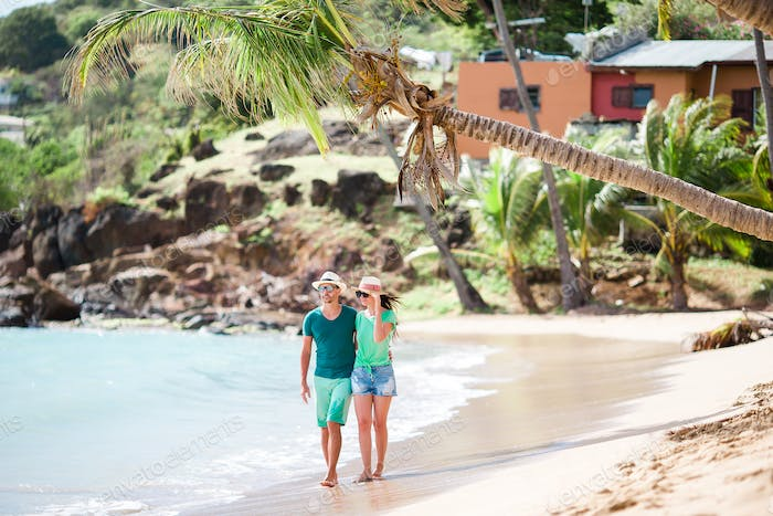 Young couple walking on tropical Carlisle bay beach with white sand and turquoise ocean water at