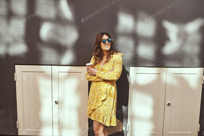 Smiling woman wearing sunglasses standing in the city drinking coffee