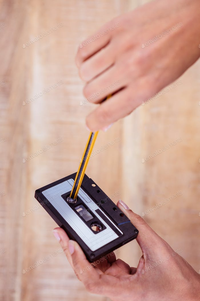 Woman rewinding old tape against wood plank