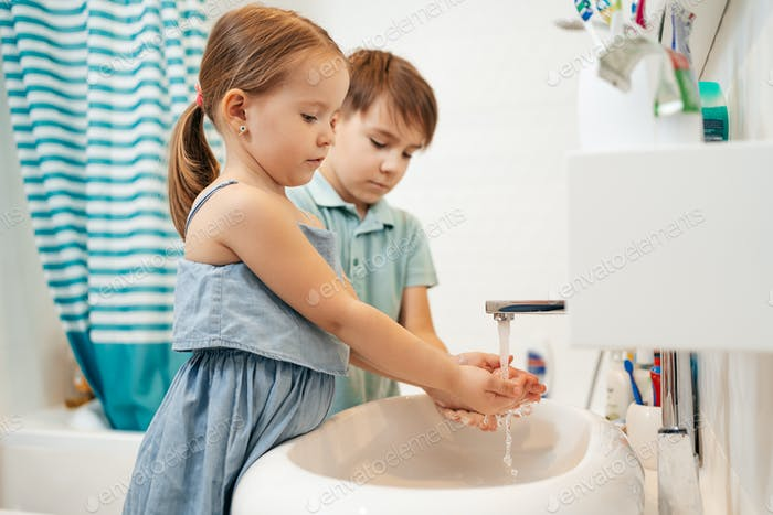 Brother and sister wash hands