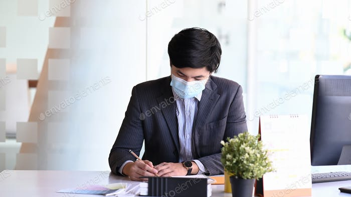 Young businessman wearing face mask concentrate writing information on document.