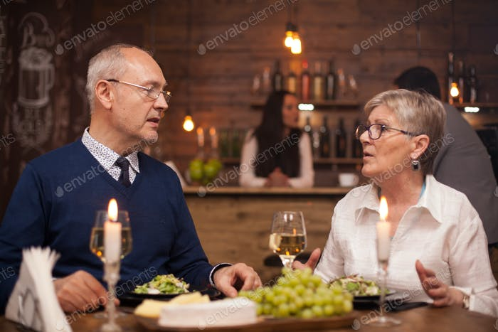 Two old friends in their sixties catching up on what they've been up to lately over dinner in a