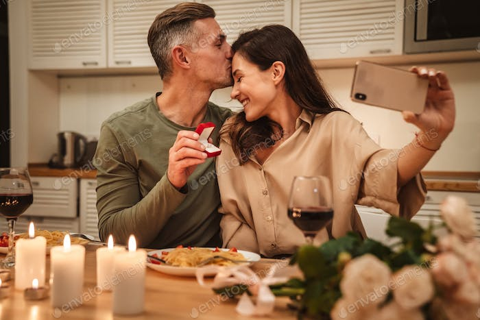 Image of couple taking selfie with engagement ring while having dinner