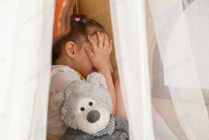 Little kid hiding behind teddy bear
