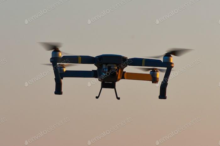 Drohne Quad-Kopter mit hochauflösender Digitalkamera fliegen Antenne über Sonnenuntergang orange Himmel