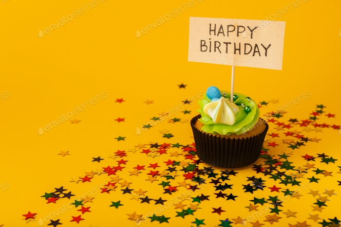Birthday cupcake with greeting card on yellow background