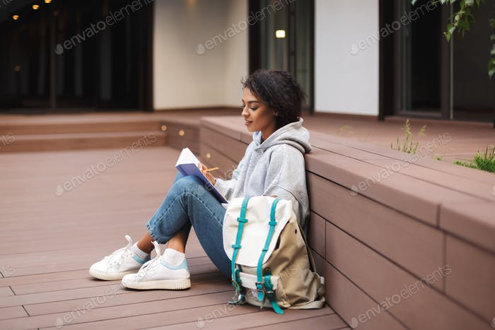 Pretty lady with dark curly hair sitting on floor and writing in notebook