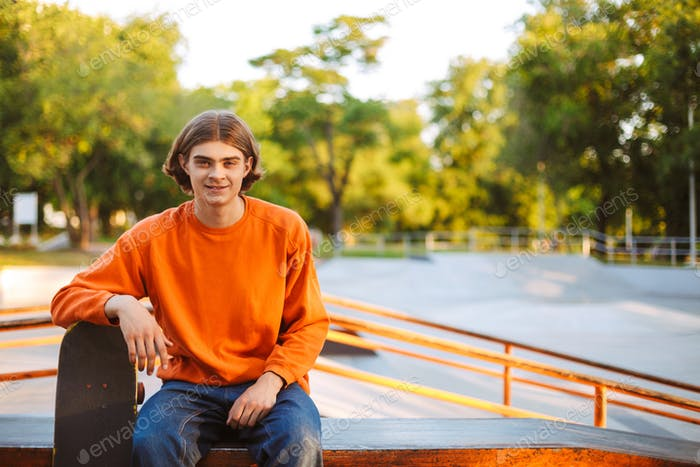 Young smiling skater in orange pullover joyfully looking in came