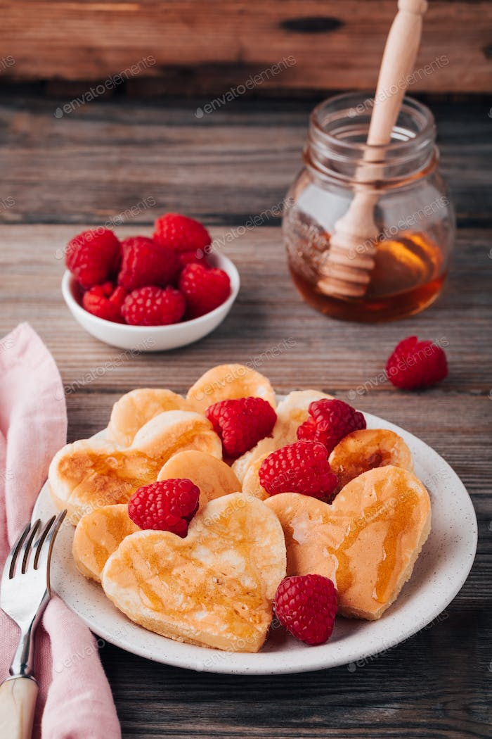 Heart shaped pancakes with raspberries and honey for St. Valentine's Day