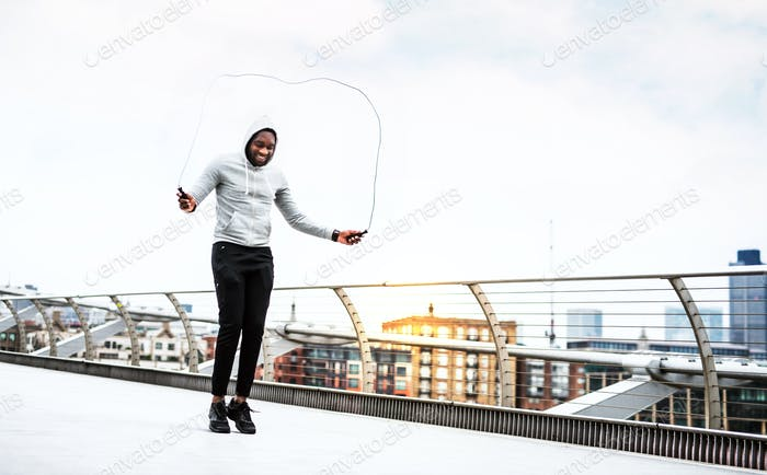 Young active black sportsman skipping with a rope in a city, wearing hoodie.