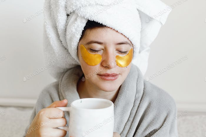 Beautiful young woman with golden eye patches and in bathrobe holding cup of coffee