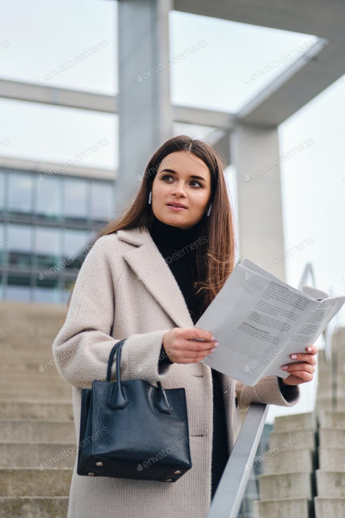 Attractive businesswoman with handbag reading newspaper outdoor