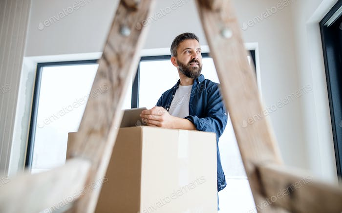 A mature man with tablet and cardboard boxes furnishing new house.