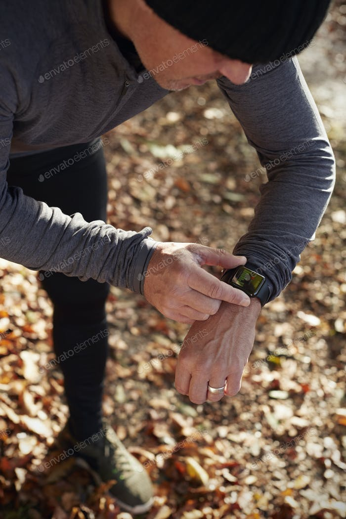 Mature Man On Autumn Run Checking Activity Tracker