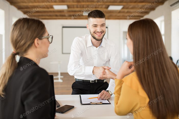 Cheerful male applicant happily shaking employer hand. Young man