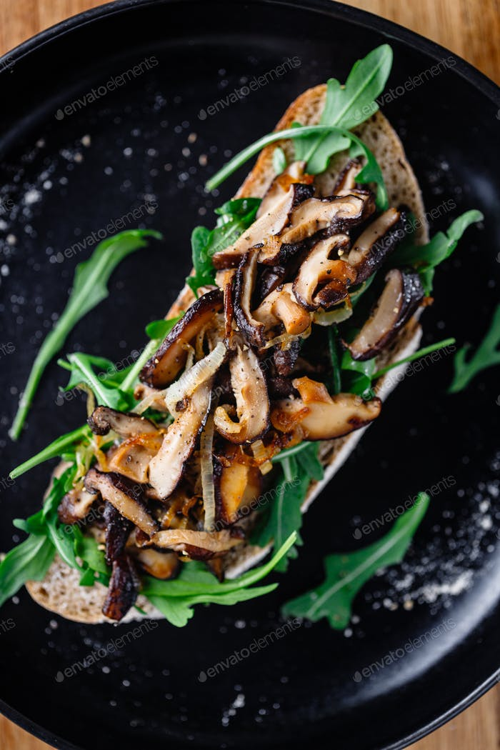 Vegan sandwich with fresh arugula, fried shiitake mushroom and shallot onion.