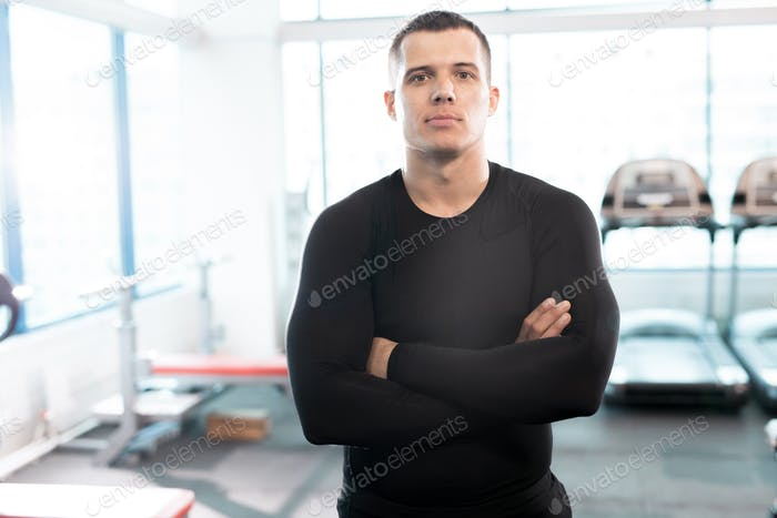 Handsome Fitness Instructor Posing in Gym