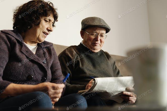 Älteres Paar liest eine Zeitung.