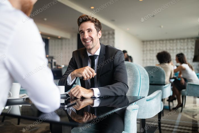 Successful businessman smiling while discussing with partner during meeting at coffee break