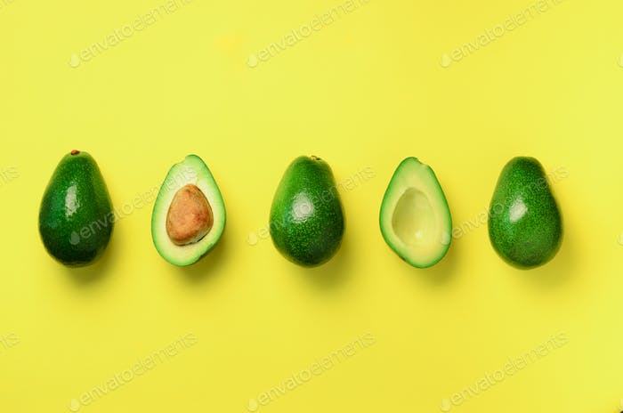 Organic avocado with seed, avocado halves and whole fruits on yellow background. Top view. Pop art
