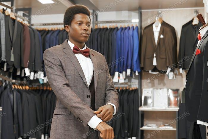 Afrikanischer Mann wählt eleganten Anzug in modischer Boutique