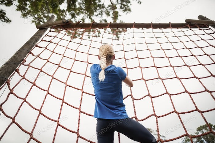 Woman climbing a net during obstacle course