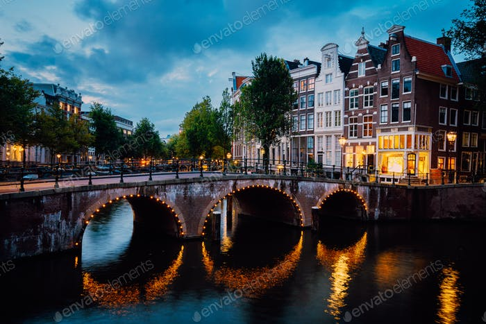 Night city view of Amsterdam canal Herengracht, typical dutch houses in evening dusk lights, Holland