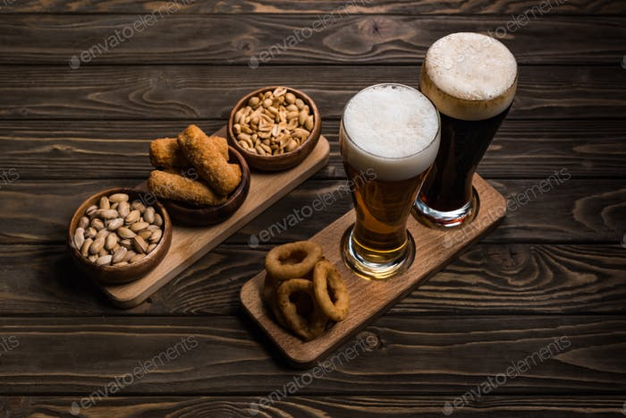 Glasses of Dark And Light Beer Near Bowls With Peanuts, Pistachios, Fried Cheese And Onion Rings