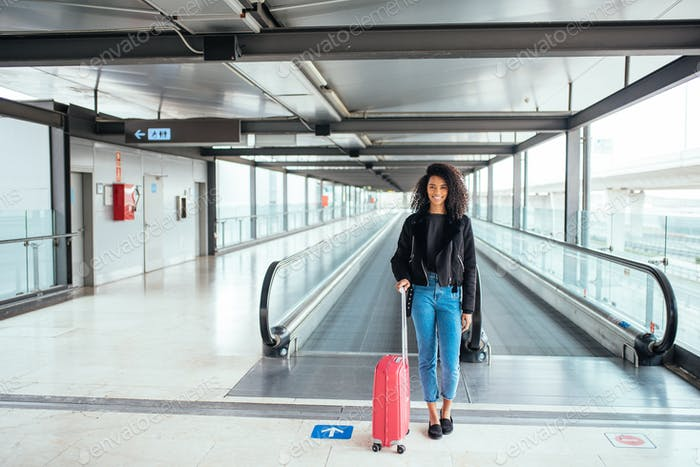 black woman in the moving walkway at the airport with a pink sui