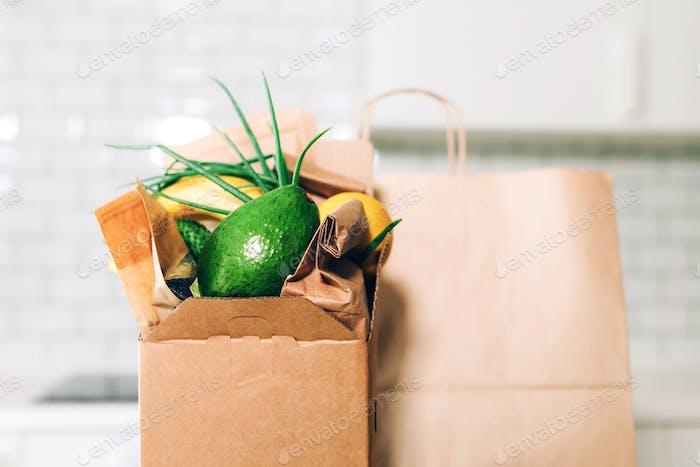 Lebensmittellieferservice während der Coronavirus-Pandemie. Lebensmittelkiste auf weißem Küchenhintergrund mit