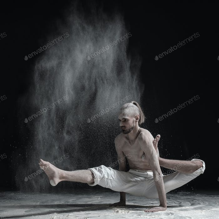 Flexible yoga man doing hand balance asana brahmachariasana.