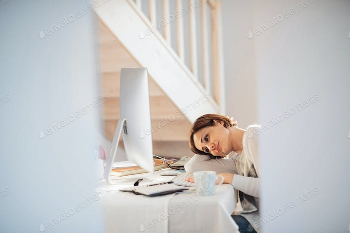 A tired young woman indoors, working in a home office.