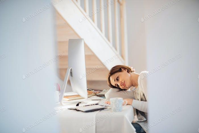 Eine müde junge Frau drinnen, die in einem Home-Office arbeitet.