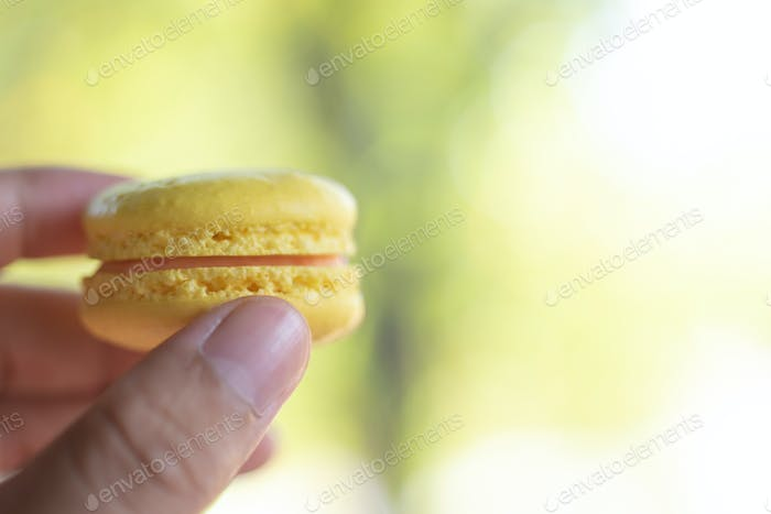 Cropped view of hand pick a yellow macaron